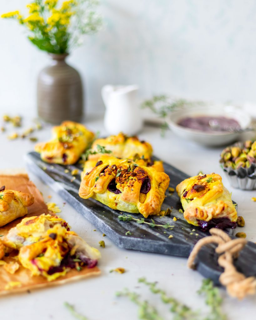 Golden Puff pastry pockets with a cherry filling. Topped with roasted pistachios, a turmeric glaze and fresh lemon thyme