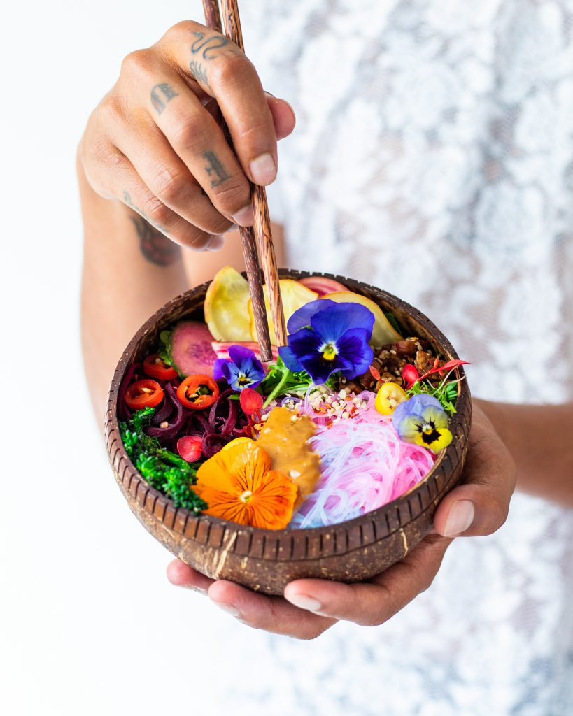Jason holding up a coconut bowl filled with colourful food