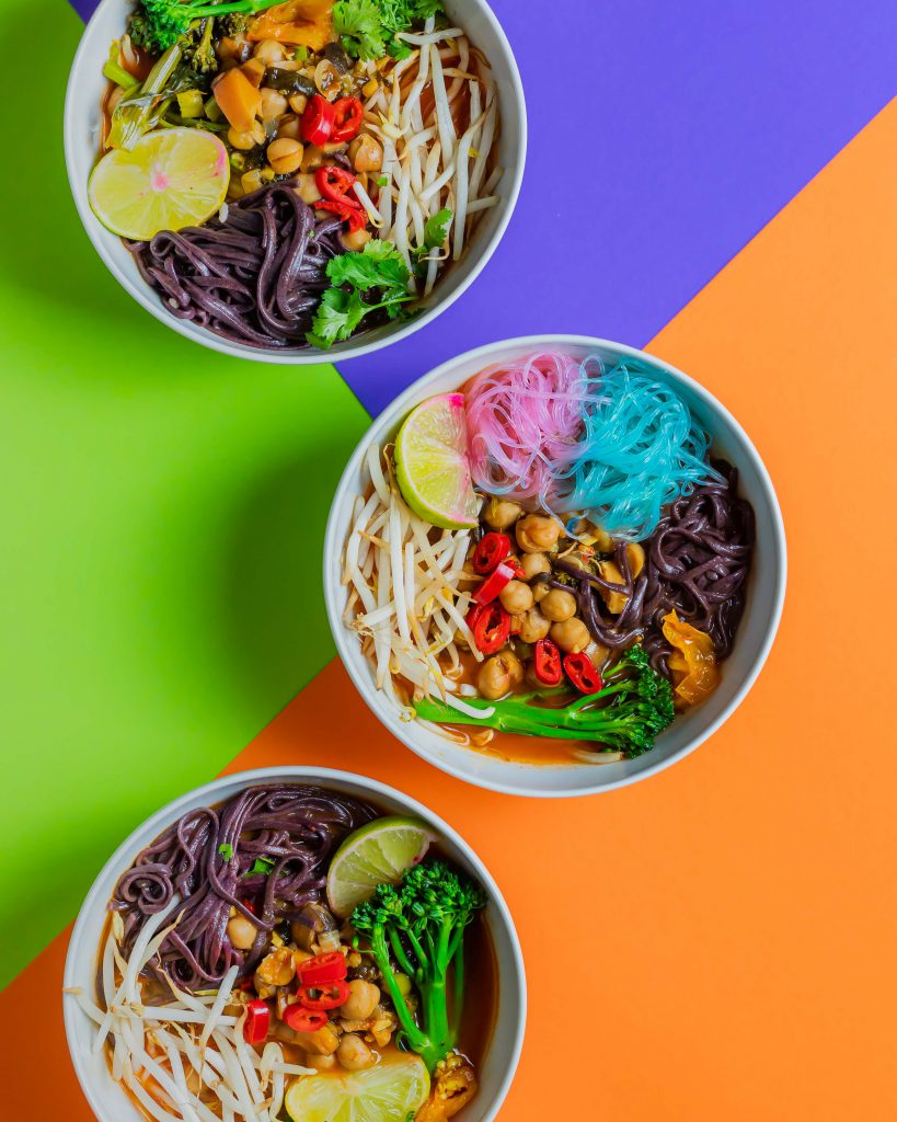 Three bowls containing the spicy soup, displayed on a colourful background.