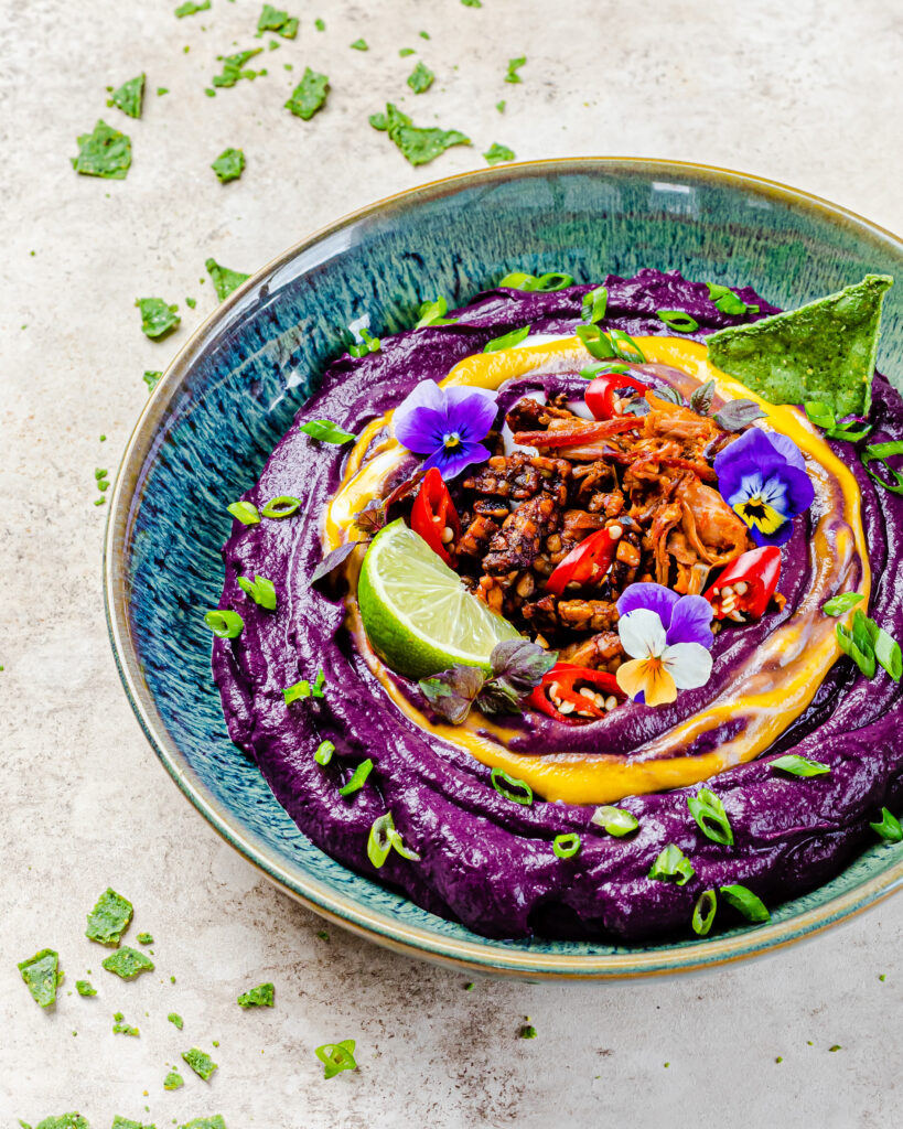 A close up of the purple carrot dip displaying all the toppings. The toppings are sweet and spicy tempeh, bbq jackfruit, scallion, edible flowers and a yellow coconut yoghurt swirl.