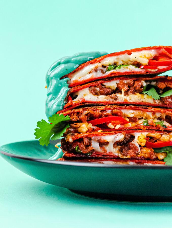 A stack of vegan quesadilla on a blue backdrop