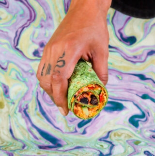 Holding a seaweed tortilla with vegan cream cheese and sun-dried tomatoes
