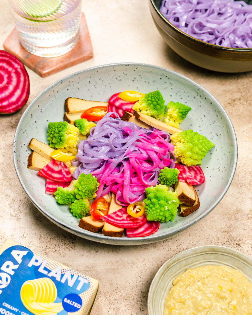 A bowl with colourful noodles, veggies and a creamy sauce